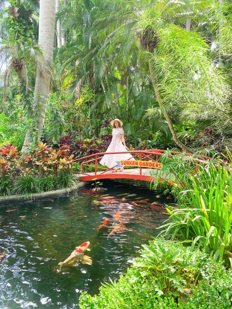 a gril in a dress poses on a red bridge at Sunken Gardens surrounded by trees and koi pond