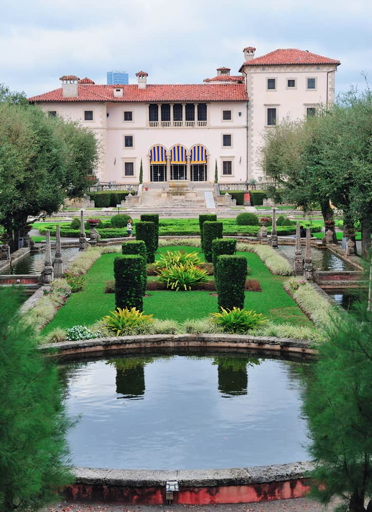 The European Gardens at vizcaya complete with reflecting ponds and statues with the home in the background