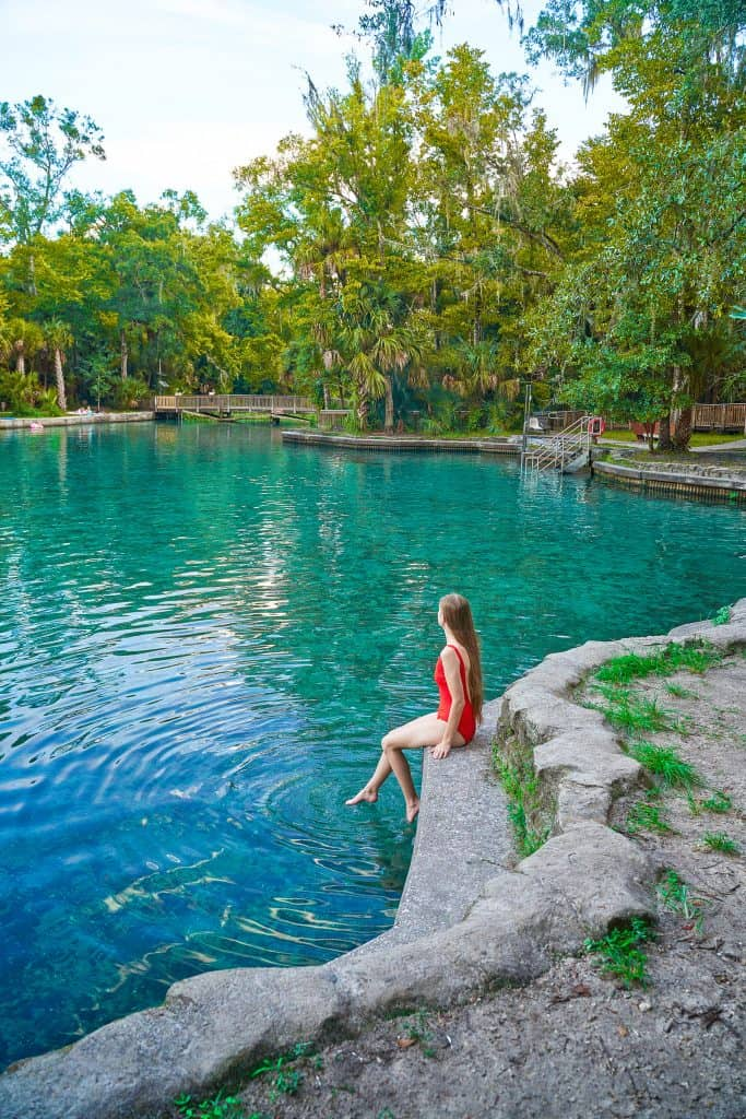 At Wekiwa Springs a girl in red swimsuit poses with her feet in the springs sitting on a concrete wall