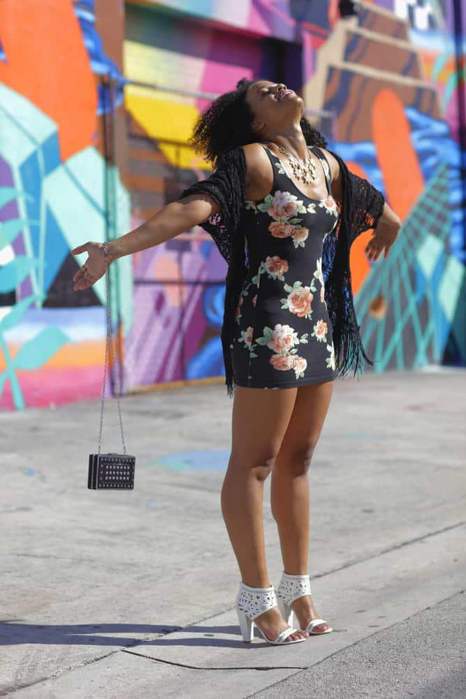 Girl in a black flower dress poses in front of a multicolored mural wall in Wynwood