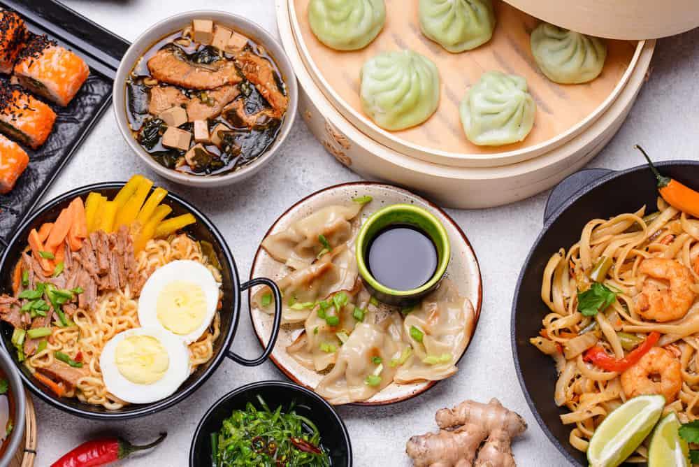 A mixture of Asian food such as dim sum, gyoza, pad thai, ramen and sushi rolls