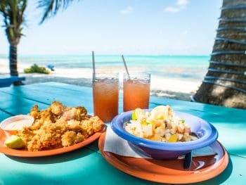a beachfront restaurant in clearwater serving conch and fried fish with ocean views on a teal picnic table