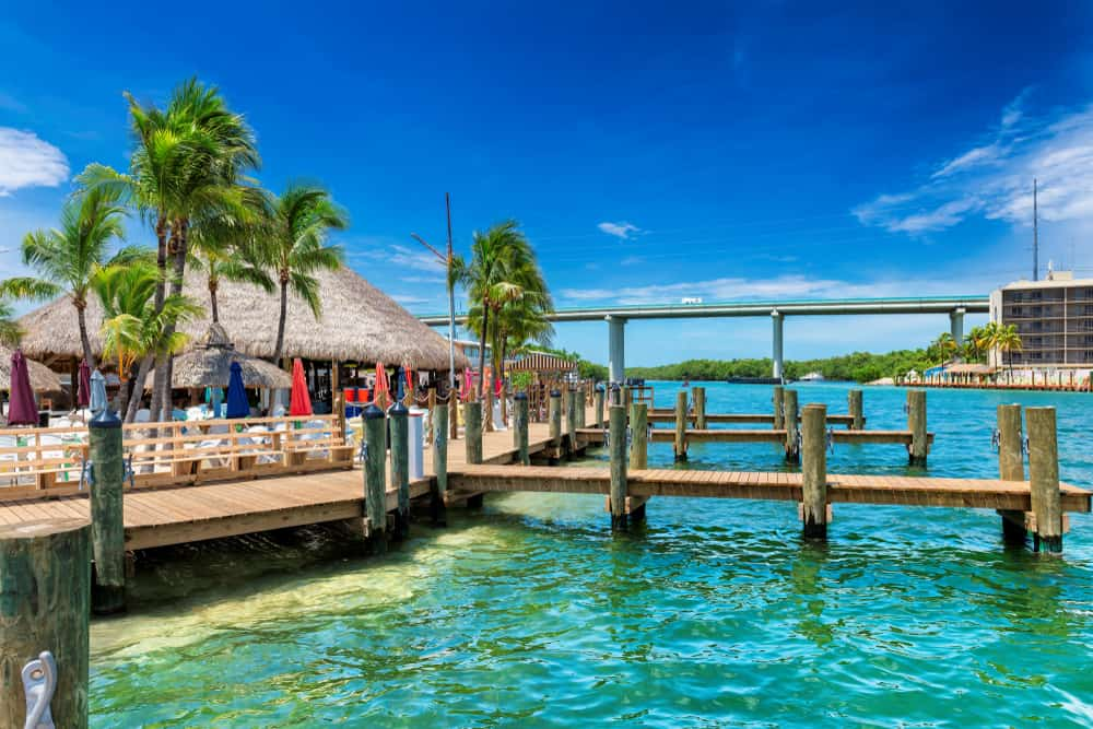 Beautiful Turquoise water in Key largo with a dock, tiki hut and bridge in background