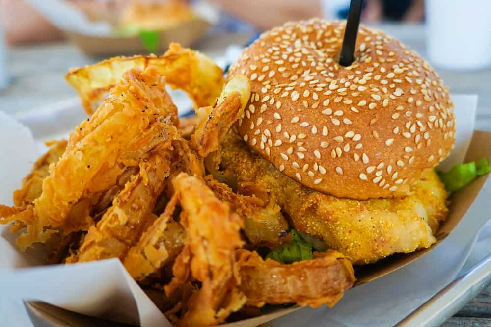a fried fish sandwich on sesame bun with fries and onion rings