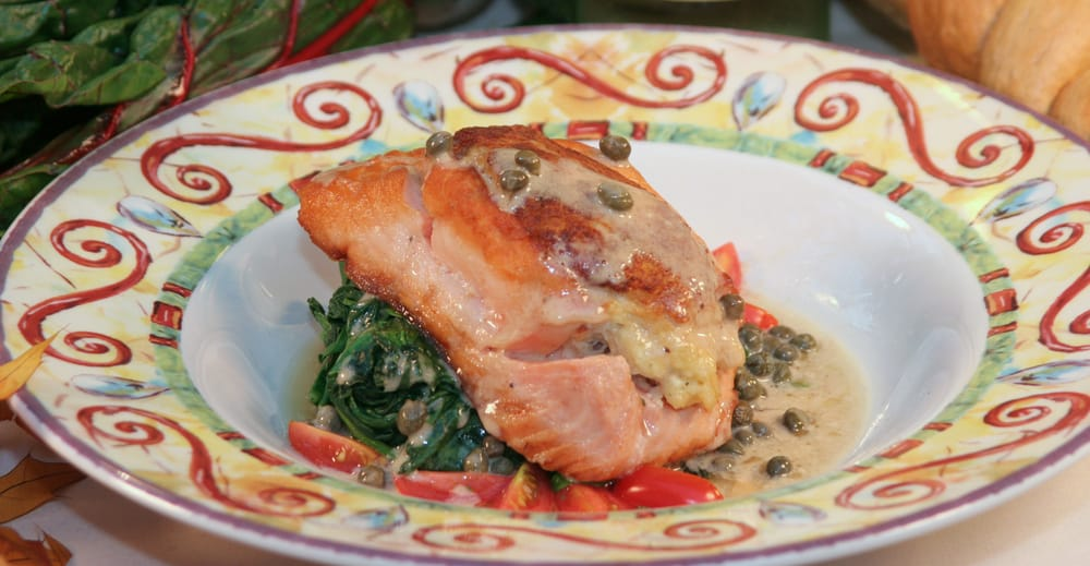 Fish with lemon caper sauce , sautéed spinach and tomatoes on a colorful plate