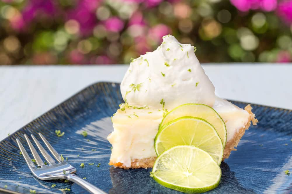 Slice of key lime pie with meringue and limes on a blue plate
