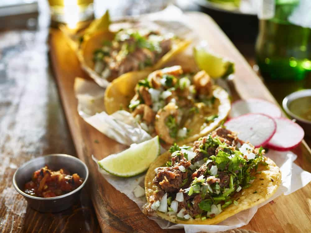 A plate of Mexican style tacos with meat cilantro and hard shell served with limes on a wood tray