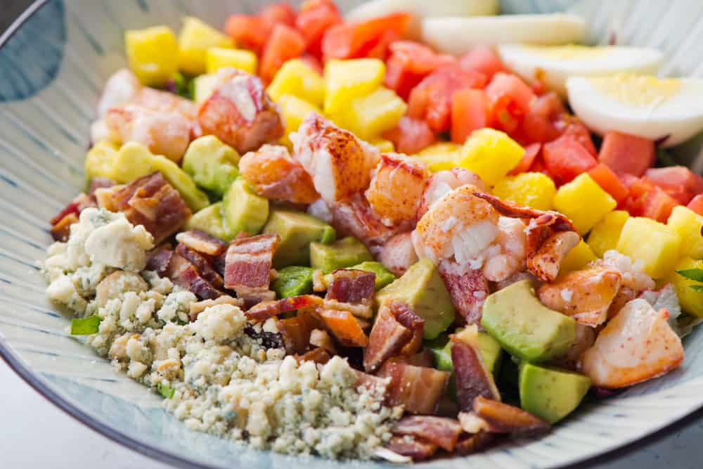 A lobster cobb salad with blue cheese, bacon, avocado, mango, tomatoes and eggs