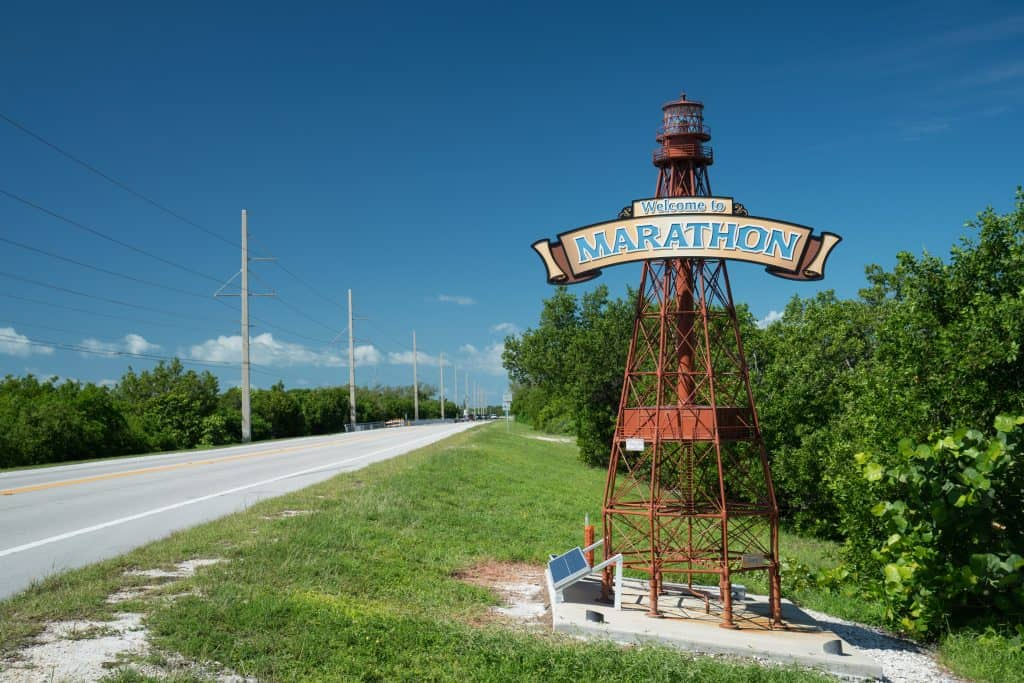 A sign shaped like a lighthouse welcomes guests to Marathon.