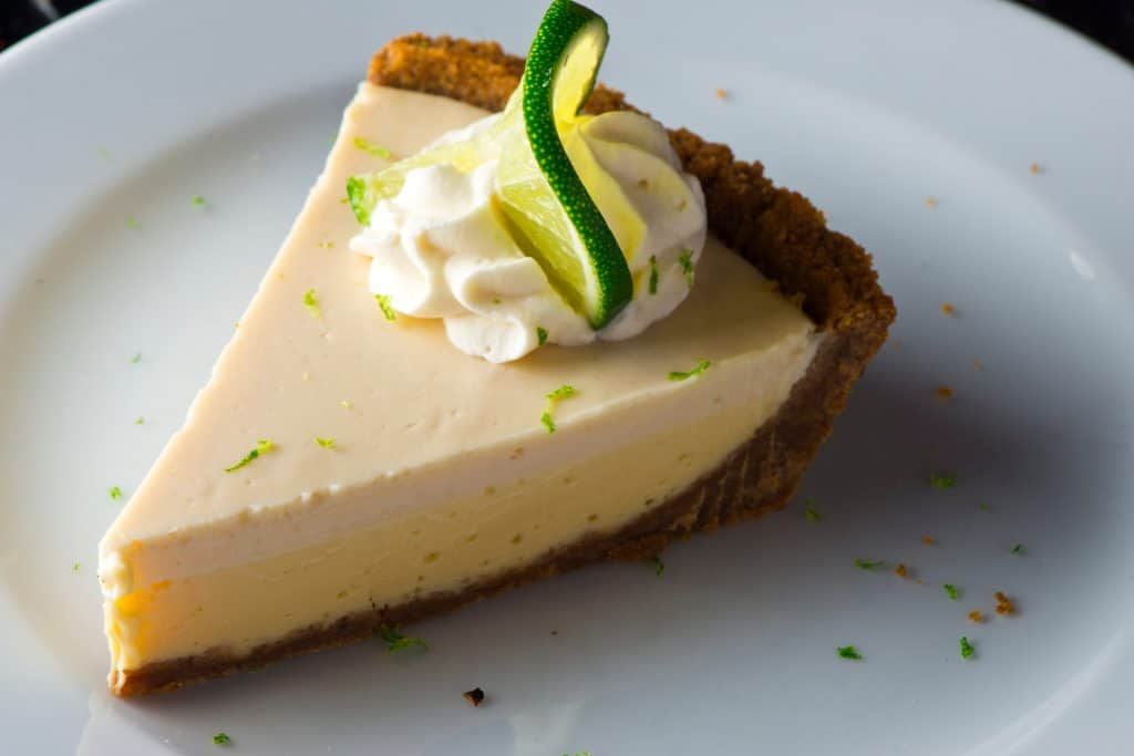 a delicious piece of Key Lime Pie rests on a plate with whipped cream.