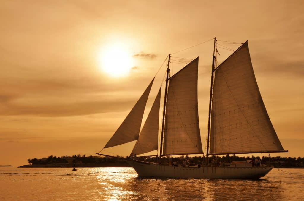 A catamaran sails through the sunset.
