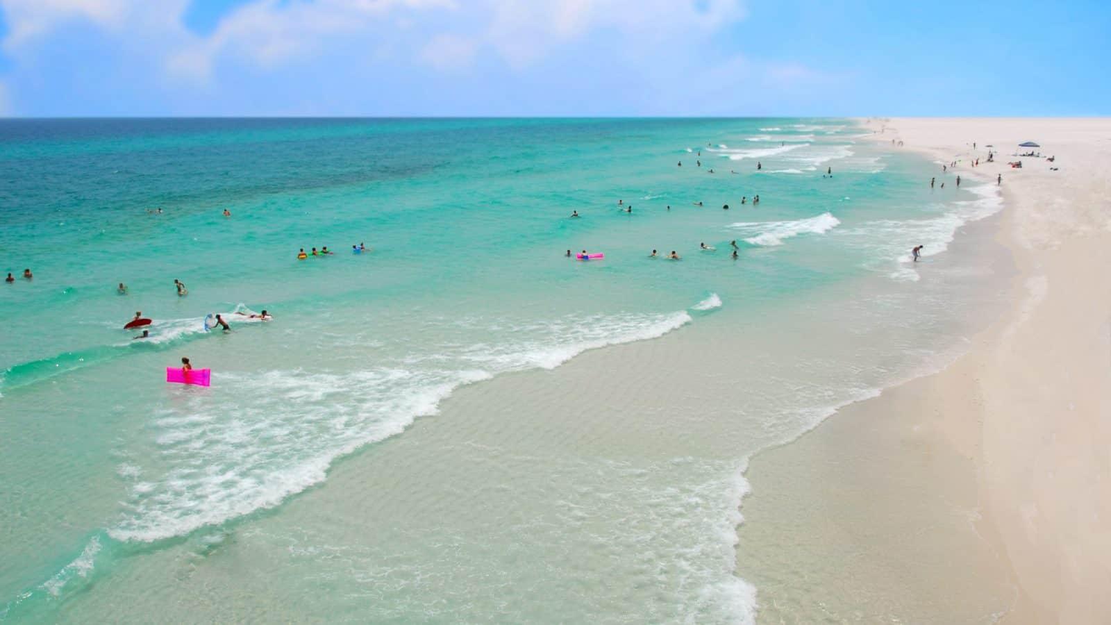 people swimming in the blue water on gulf islands national seashore with a blue sky