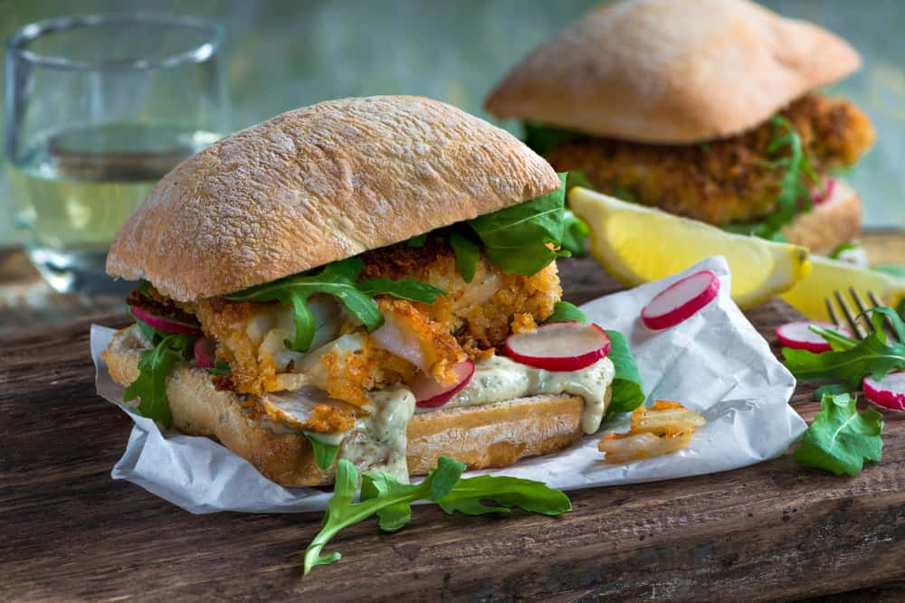 A fish sandwich with radishes, ciabatta bread and aregula on a wooden tray