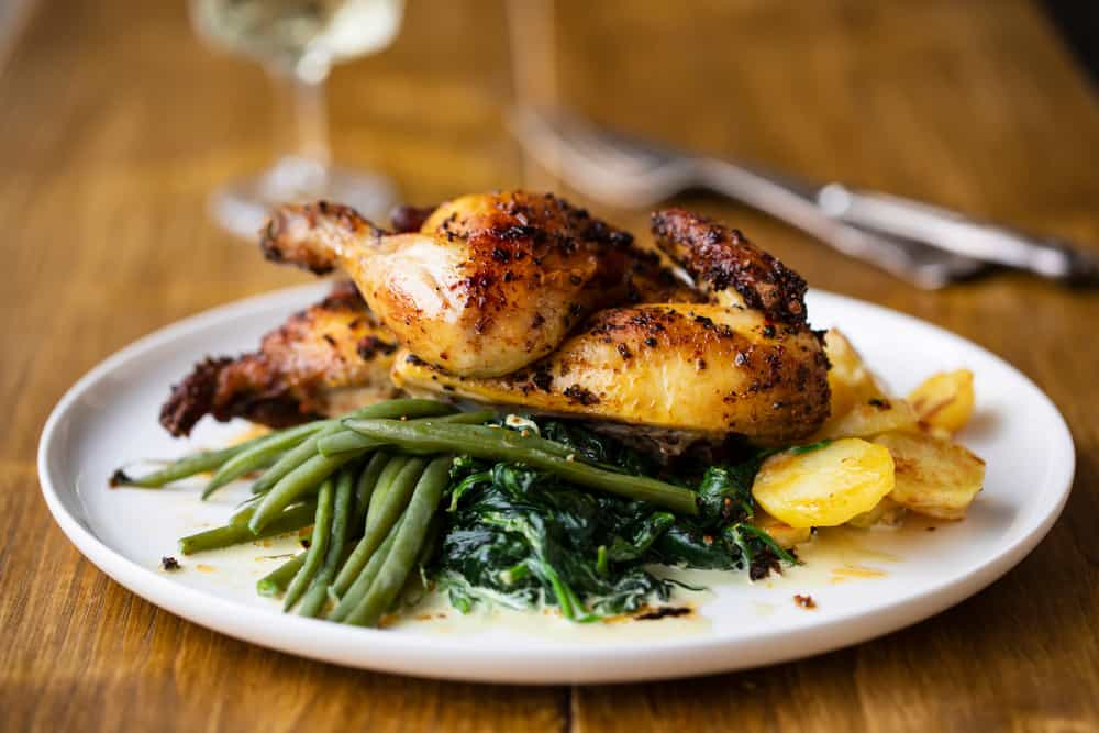 Chicken in a herb sauce with sautéed green beans and spinach with roasted potatoes