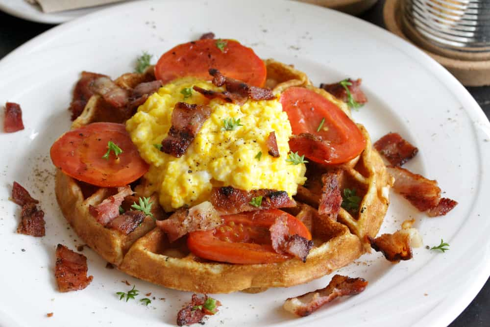 A waffle topped with bacon, tomatoes and eggs