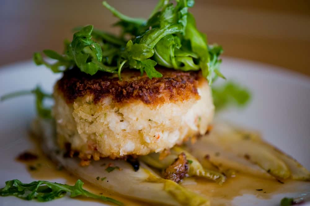A jumbo lump crab cake over wilted endives topped with greens