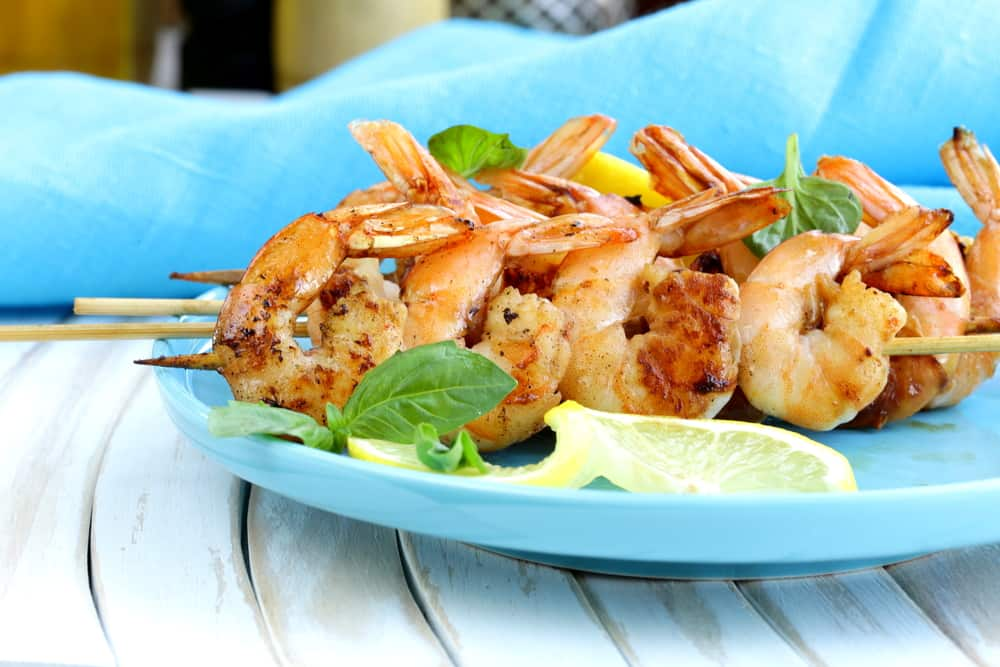 Jumbo shrimp skewers on a blue plate with a slice of lemon