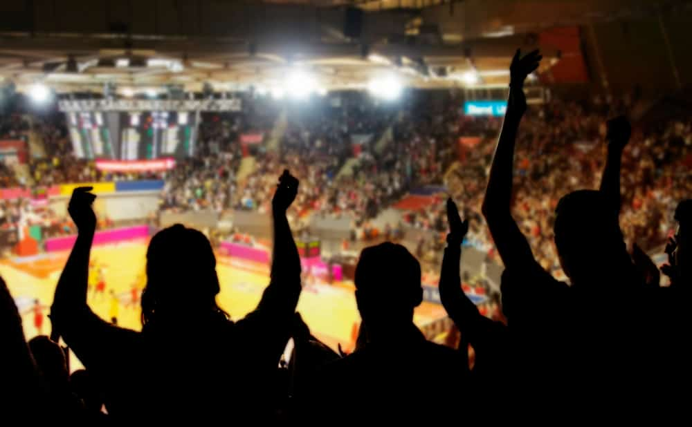 photo of silhouette of fans at a basketball game