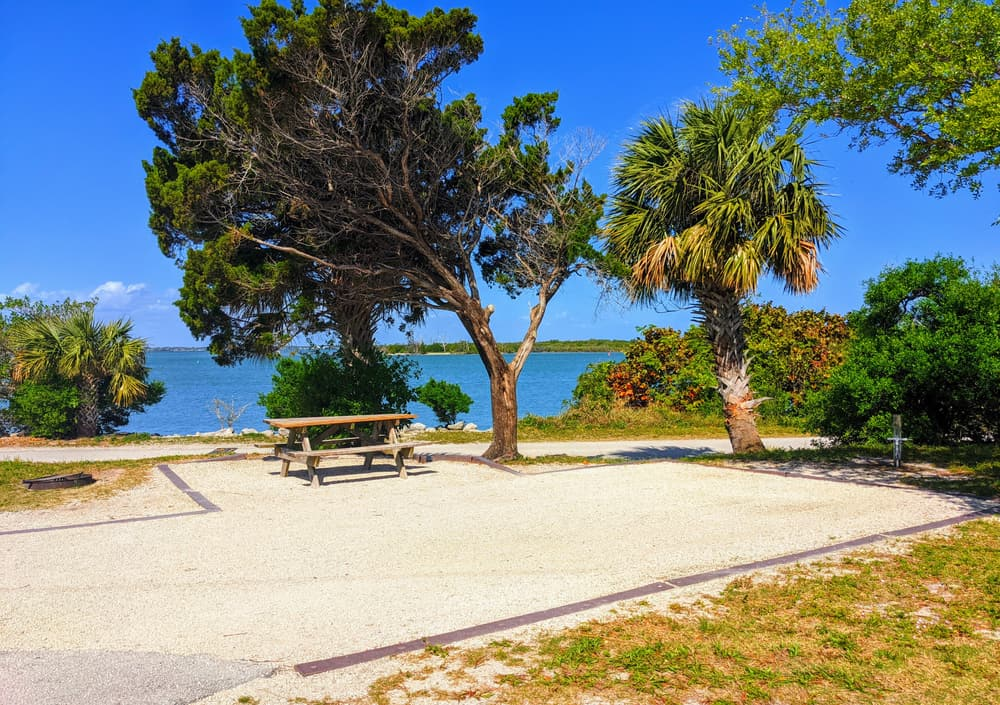 AN empty waterfront gravel camping site with picnic table