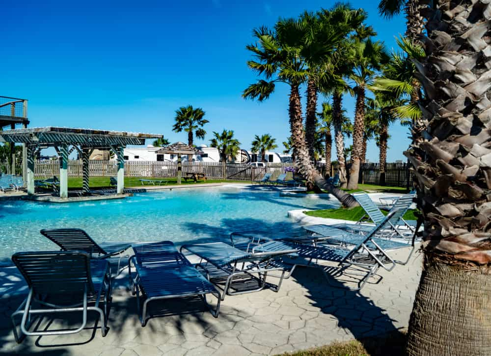 an RV resort with  pool, chairs, cabanas and motorhomes in the back