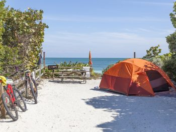 an orange tent with two bikes overlooking the ocean