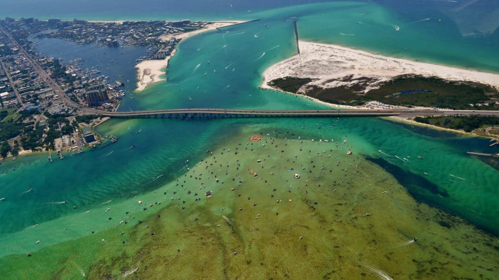 A drone image shows the sandbar of Crab Island adjacent to the Destin Harbor bridge.