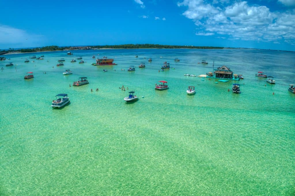 Sunbathers and swimmers stand in the shallow waters of Crab Island, Florida.