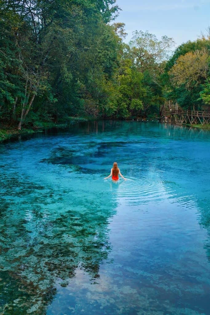 Girl in a red swimsuit in the blueish water of the springs surrounded by trees on the left and wooden boardwalk on the right