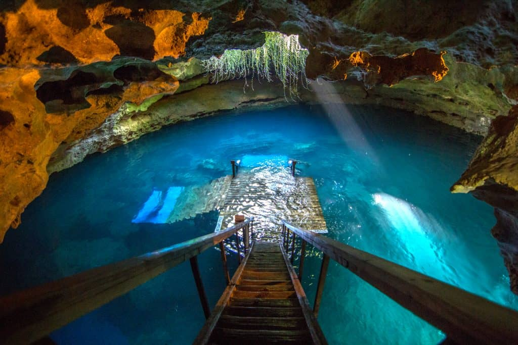 A wooden staircase descends down into the turquoise water at Devils den with sun beam steaming in the water