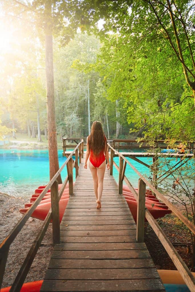 Girl in a red swimsuit walking down a wooden boardwalk at Gilchrist springs with red canoes underneath dock and turquoise water.