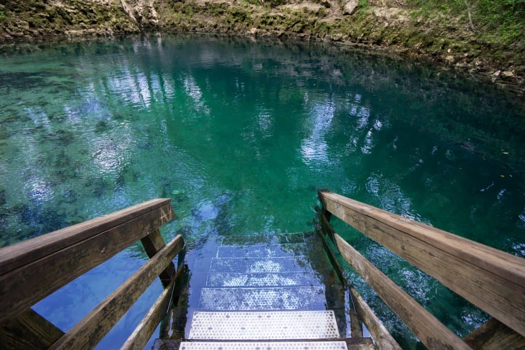 A wooden platform leads into the turquoise water at the springs with limestone walls.