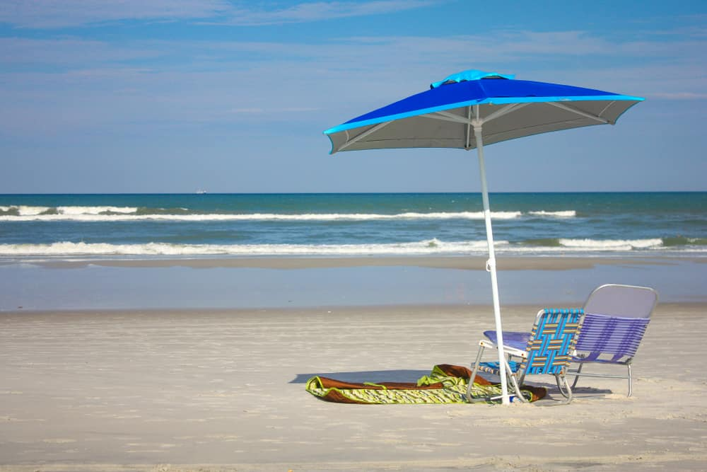 An umbrella and beach chairs on Neptune Beach one of the best beaches in Jacksonville.