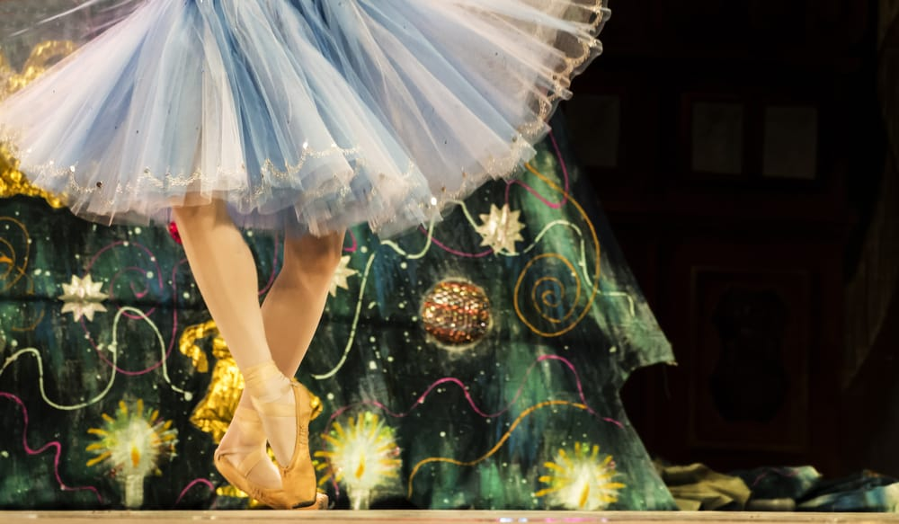 A ballet pose with a Christmas tree in the background.