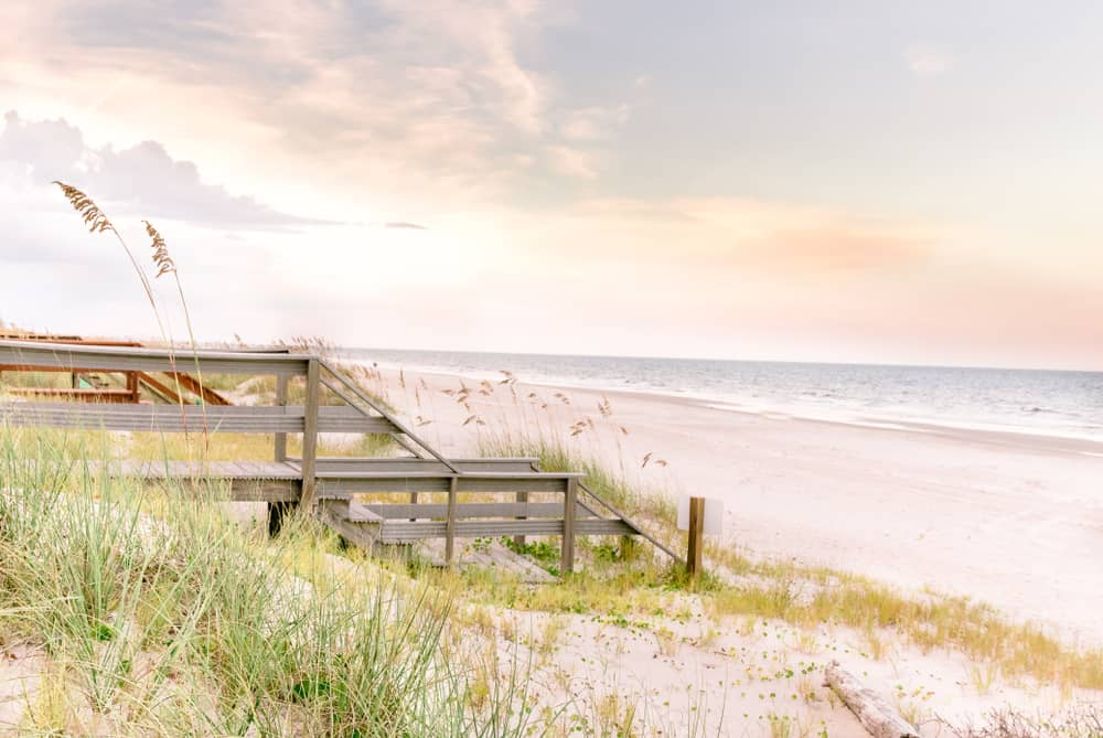 boardwalk and sand dunes on ameila island in florida during sunrise