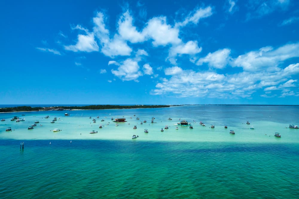 Boats gather over shallow blue green waters at beautiful crab island in  destin florida