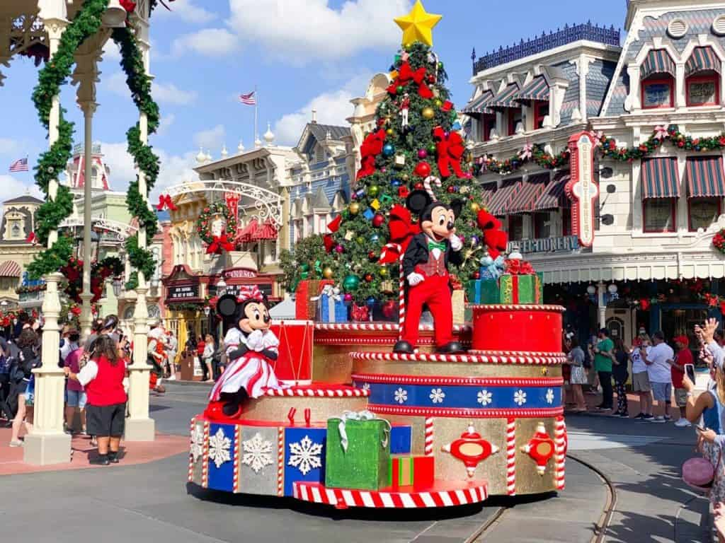 Christmas parade at the Magic Kingdom with Minnie and Mickey on a float with a tree and presents.
