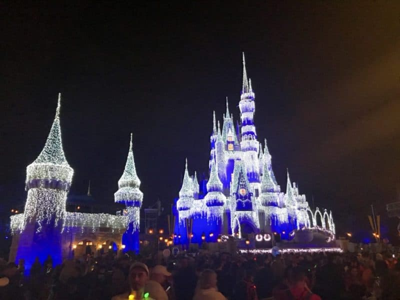 Cinderella's castle at the Magic Kingdom at night, all lit up with blue and white lights.
