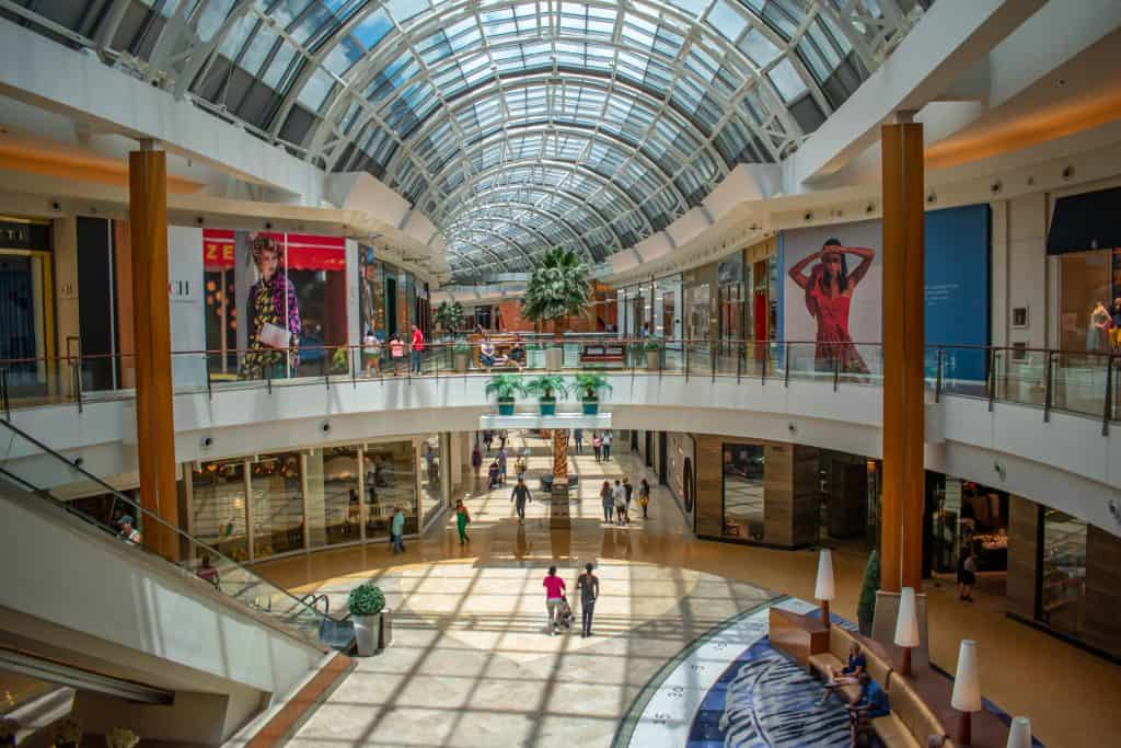 The two-story interior of a mall with guests browsing storefronts under the glass ceiling.