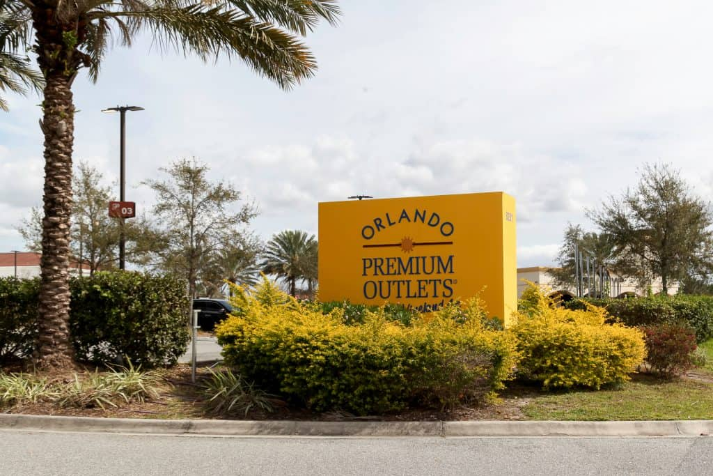 The yellow Orlando Premium Outlets sign under a palm tree.