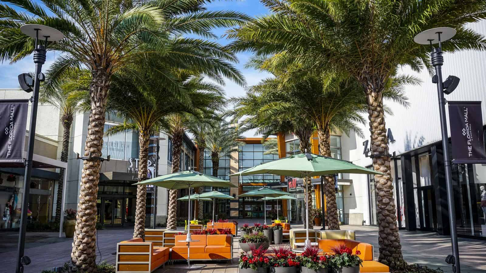 orange chairs and palm trees outside of one of the malls in orlando