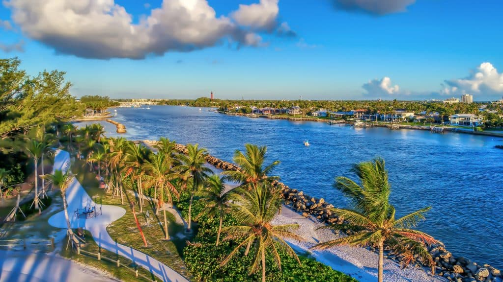 The beautiful blue waters, paved trails, and swaying palm trees of Dubois Park, one of the best things to do in Jupiter.