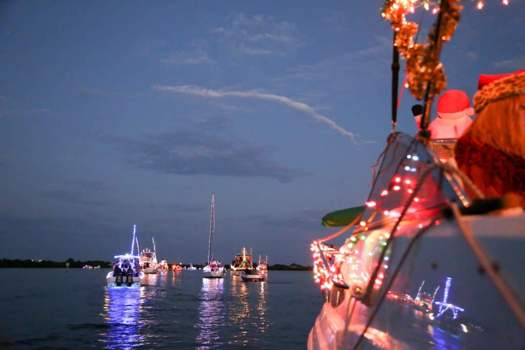 Boats in a lake covered in Christmas lights