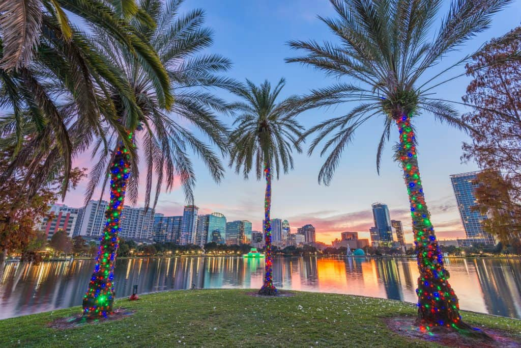 Christmas light-covered palm trees in front of a city skyline