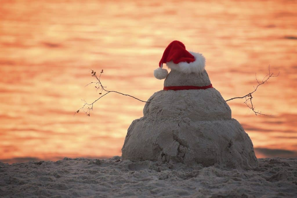 A snowman made out of sand with a Santa hat