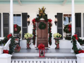 The front porch of a Key West home is decorated with red bows and wreaths, making them ready for Key West in December!