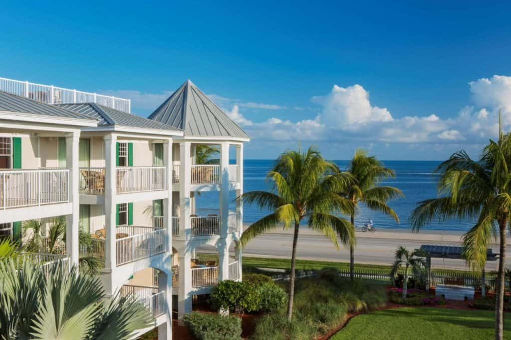 The Hyatt Residents Club in Key West features balconies that look over blue waters next to tall palm trees.