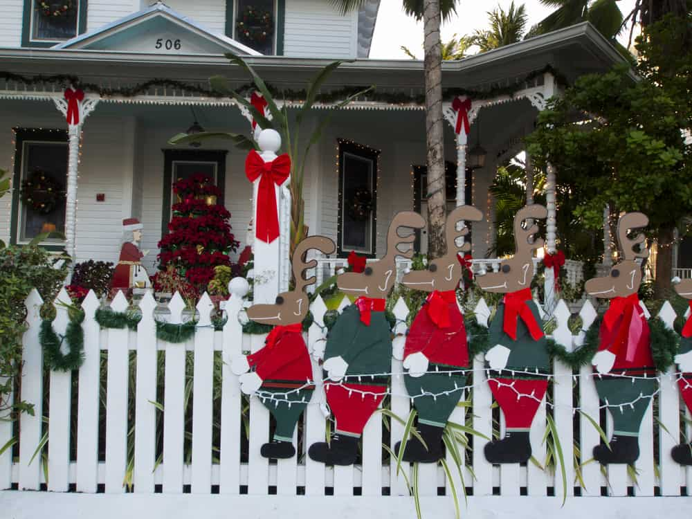 A resident't front yard is decorated for Key West in December with lots of raindeer!