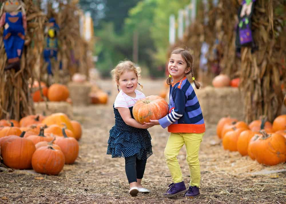Two young girls carrying a pumpkin at a pumpkin patch decorated for fall.
