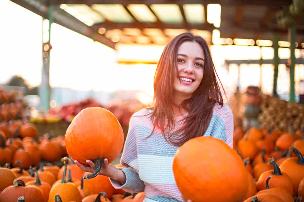 A young woman smiling while holding two pumpkins at a pumpkin patch.