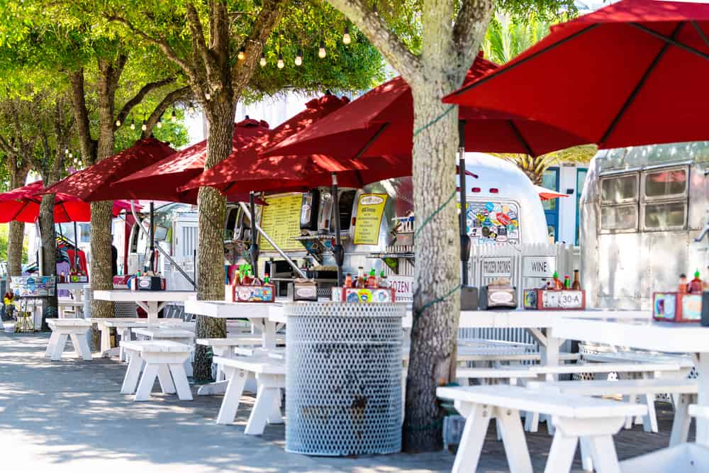 Picnic tables and umbrellas set up outside gourmet food trucks parked on Airstream Row, one of the best things to do in Seaside, Florida.